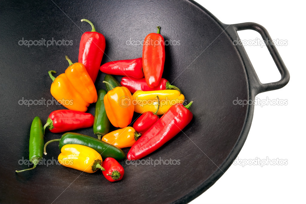 Colorful sweet and jalapeno peppers in a black cast iron wok — Stock Photo #1999555