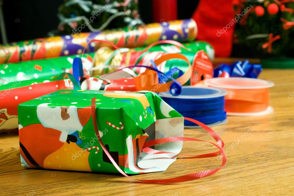 Christmas gift wrapping paper and ribbon with a small partially wrapped package — Stock Photo #2073803