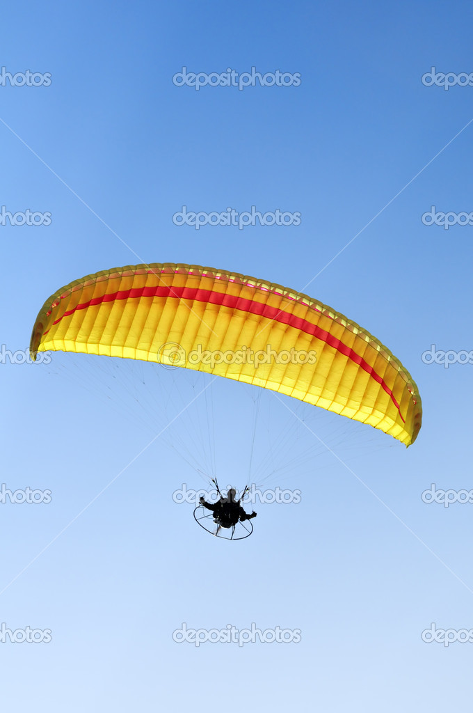 Man with a yellow paraglider flying in the sky — Stock Photo #1978038