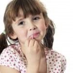Little girl putting on lip gloss — Stock Photo