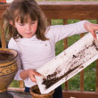 Little girl playing with pots and soil — Stock Photo