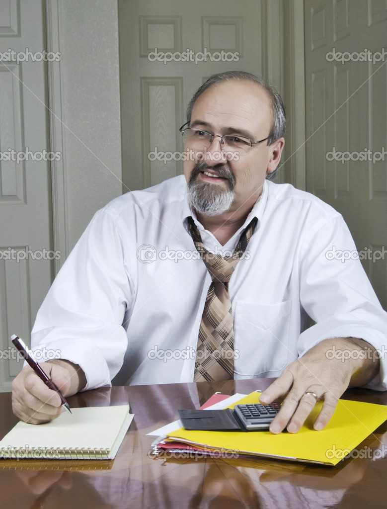 Businessman smiling as he works with a client at his desk — Stock Photo #1984112