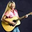 Pretty blonde woman playing guitar — Stock Photo