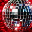 图库照片: Mirror Disco globe - isolated on red