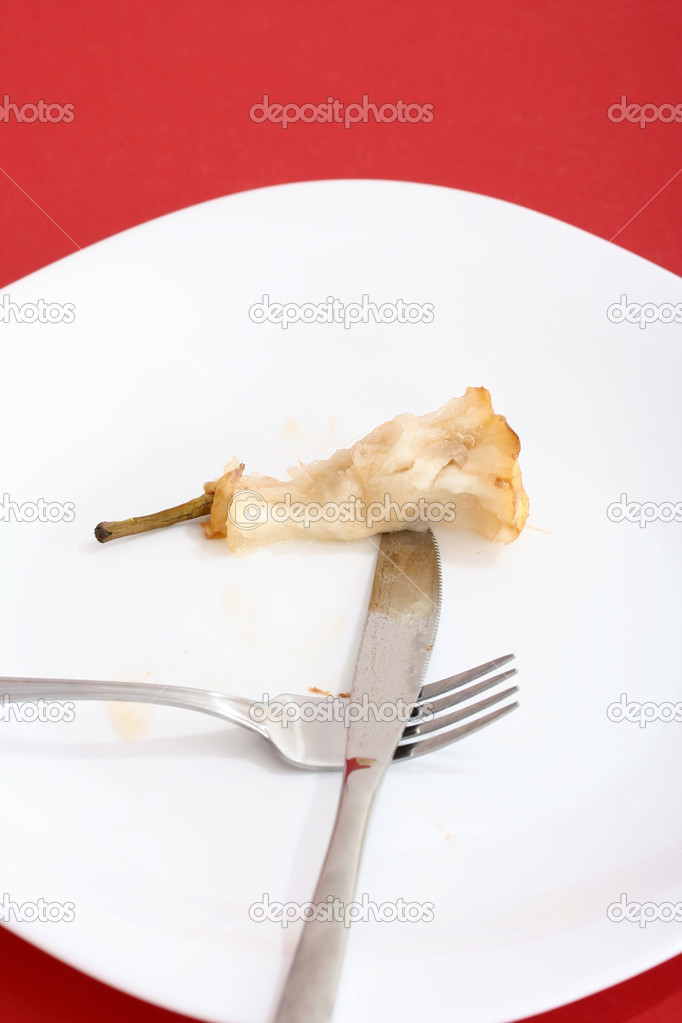 Pear core on a white plate.  Stock Photo #1983595