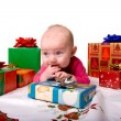 Baby Lying Amongst Christmas Gifts - Stock Photo