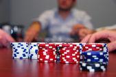 Poker žetony s hráči v pozadí — Stock fotografie