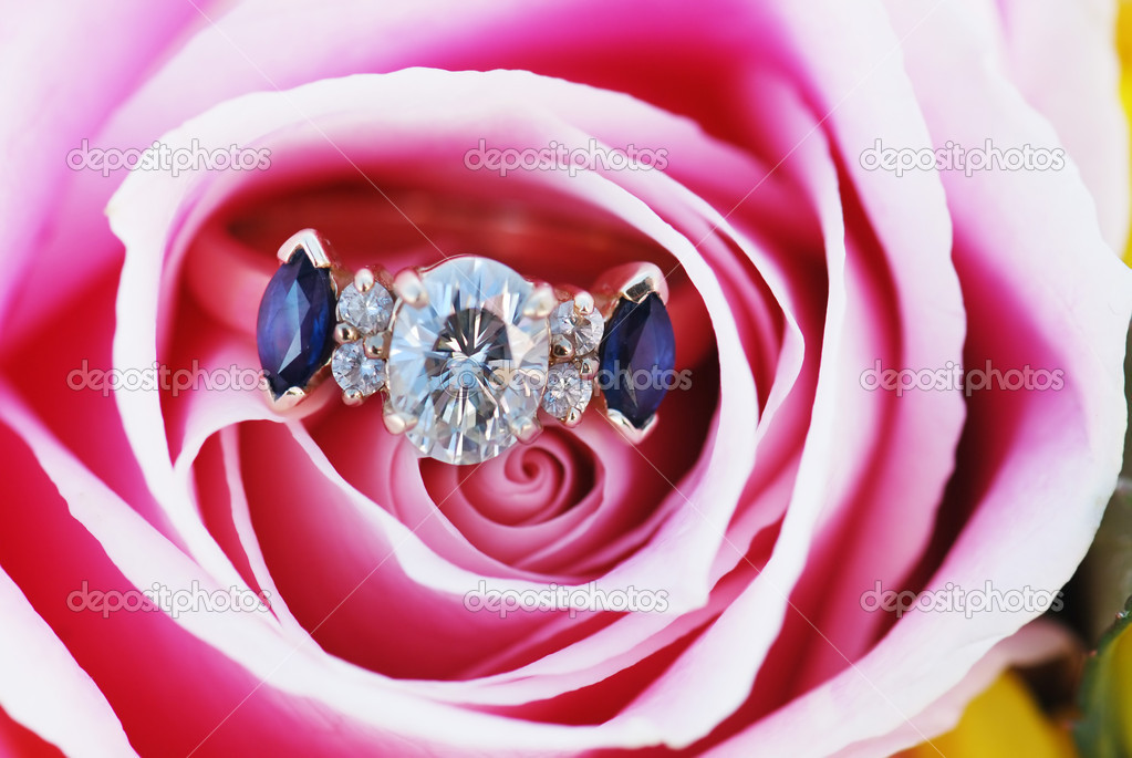 An engagement ring sits in the folds of delicate pink rose. — Stock Photo #2352945