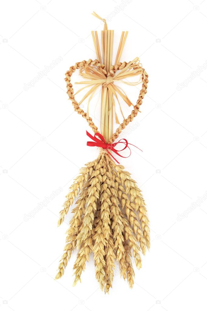 Corn dolly with heart shape fertility symbol with red ribbon bow, isolated over white background. — Stock Photo #1980877