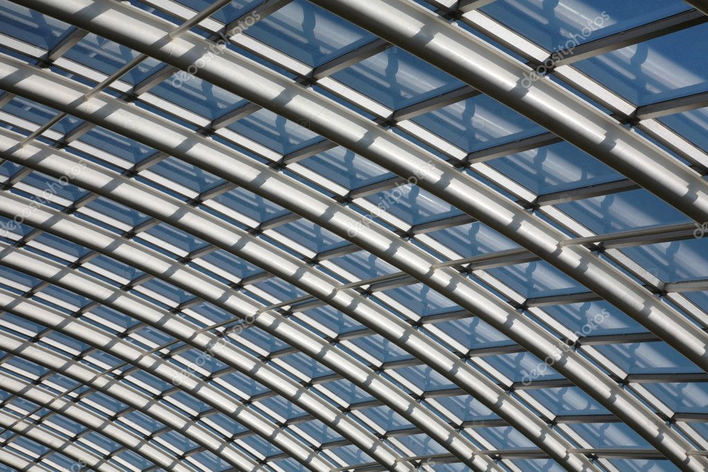 Conservatory roof span with curved metal joists and glass window panes against a blue sky. — Stock Photo #2615381