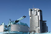 Old naval guns against modern building. — Stock Photo