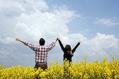 Young couple in a rape field — Foto Stock