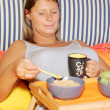 Young blond woman in bed for breakfast — Stock Photo