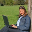 Cute young girl with laptop outdoors — Foto Stock