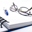 Notebook with pen and glasses — Stock Photo