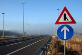 Signs in foggy motorway — Stock Photo