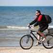 Stock Photo: Man riding mountain bike on the beach