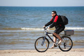 Man riding mountain bike on the beach — Stock Photo