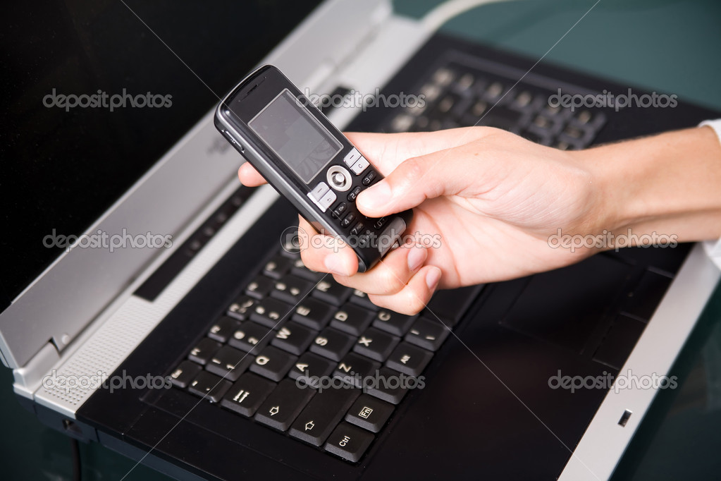Woman holding cell phone over the notebook's keyboard  Stock Photo #2022822