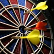Dart boart with three darts - Stock Photo