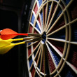 Dart board with three darts - Foto Stock