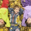 Kids lying down on the leaves - Stock Photo