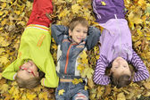 Kids lying down on the leaves — Stock Photo