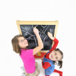 Two little girls and blackboard — Stock Photo