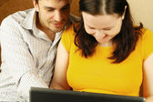 Happy young couple using a laptop — Stock Photo