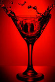 Red glass of martini with splash — Stock Photo
