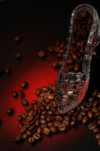 Crystal shoe with coffee on a red — Stock Photo