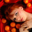 Young woman portrait with many oranges — Stock Photo