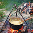 Pot with polenta on a campfire - Stock Photo