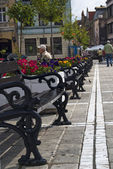 Simetrical string of benches in a market — Stock Photo
