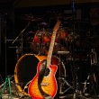 Acoustic guitar and drums on stage — Stock Photo #2279518