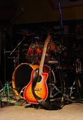 Acoustic guitar and drums on stage — Stock Photo