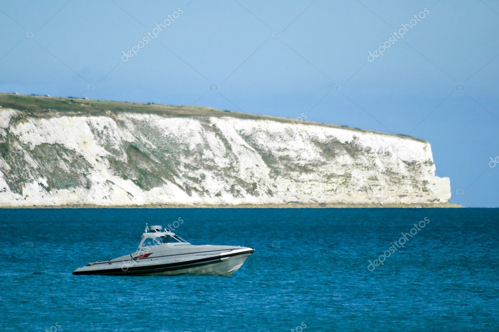 Speedboat anchored beneath a white cliff coastline — Stock Photo #2182414