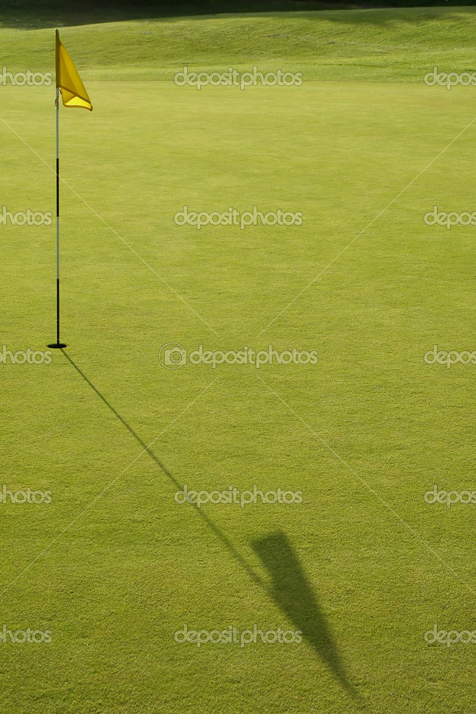 Long flag shadow across a golf putting green — Stok fotoğraf #2183007