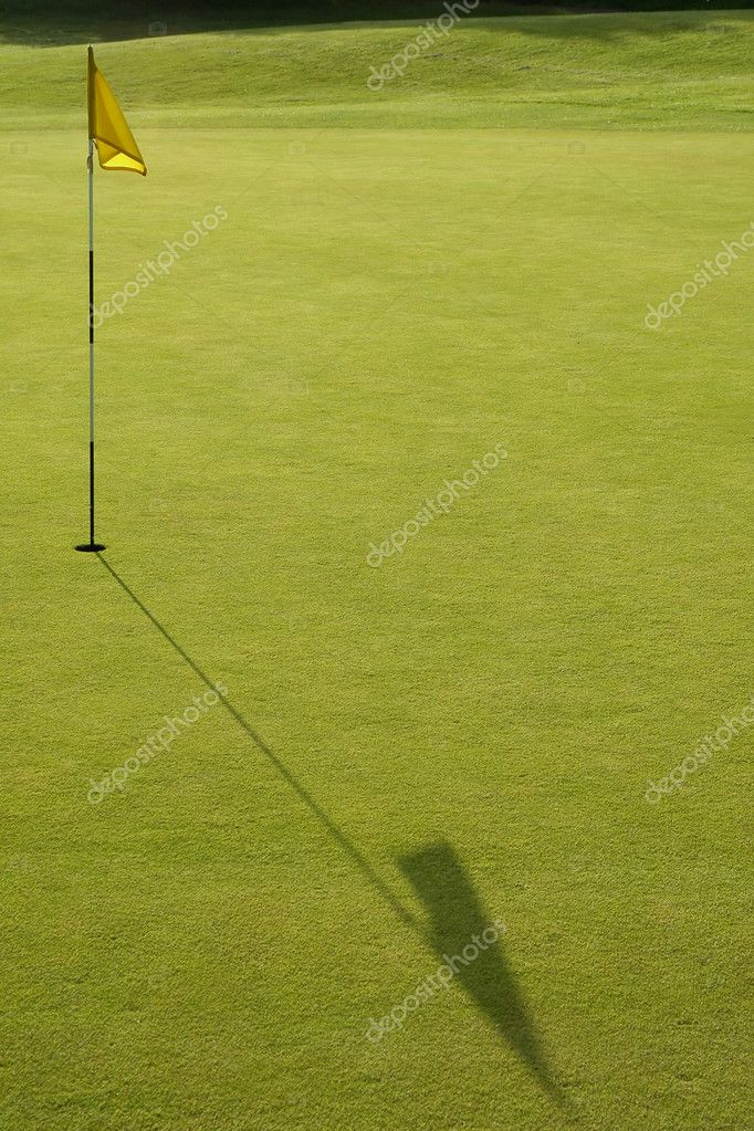 Long flag shadow across a golf putting green — Lizenzfreies Foto #2183007