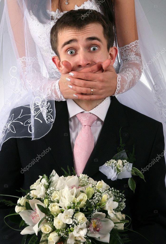 Wedding portrait of the groom with bride on background with hands covering mouth  Foto de Stock   #1941317