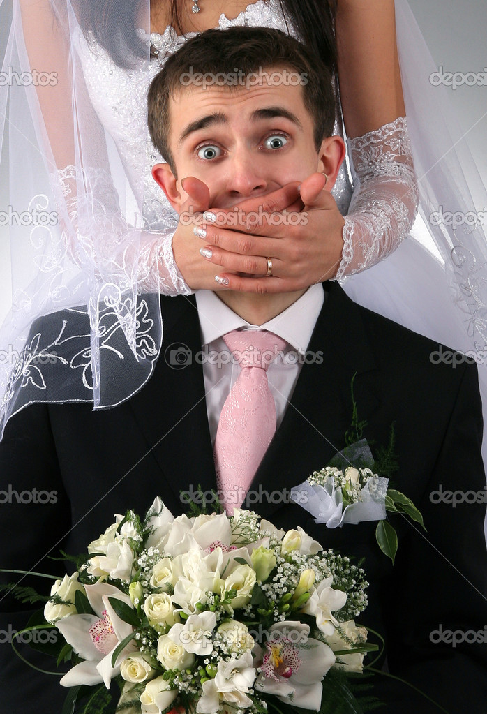 Wedding portrait of the groom with bride on background with hands covering mouth  Stockfoto #1941317