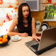 Woman on the kitchen with laptop — Stock Photo