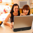 Two women on the kitchen with laptop — Stock Photo