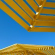 Foto Stock: Yellow sunshade and blue sky