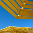 Yellow sunshade and blue sky — Stock Photo