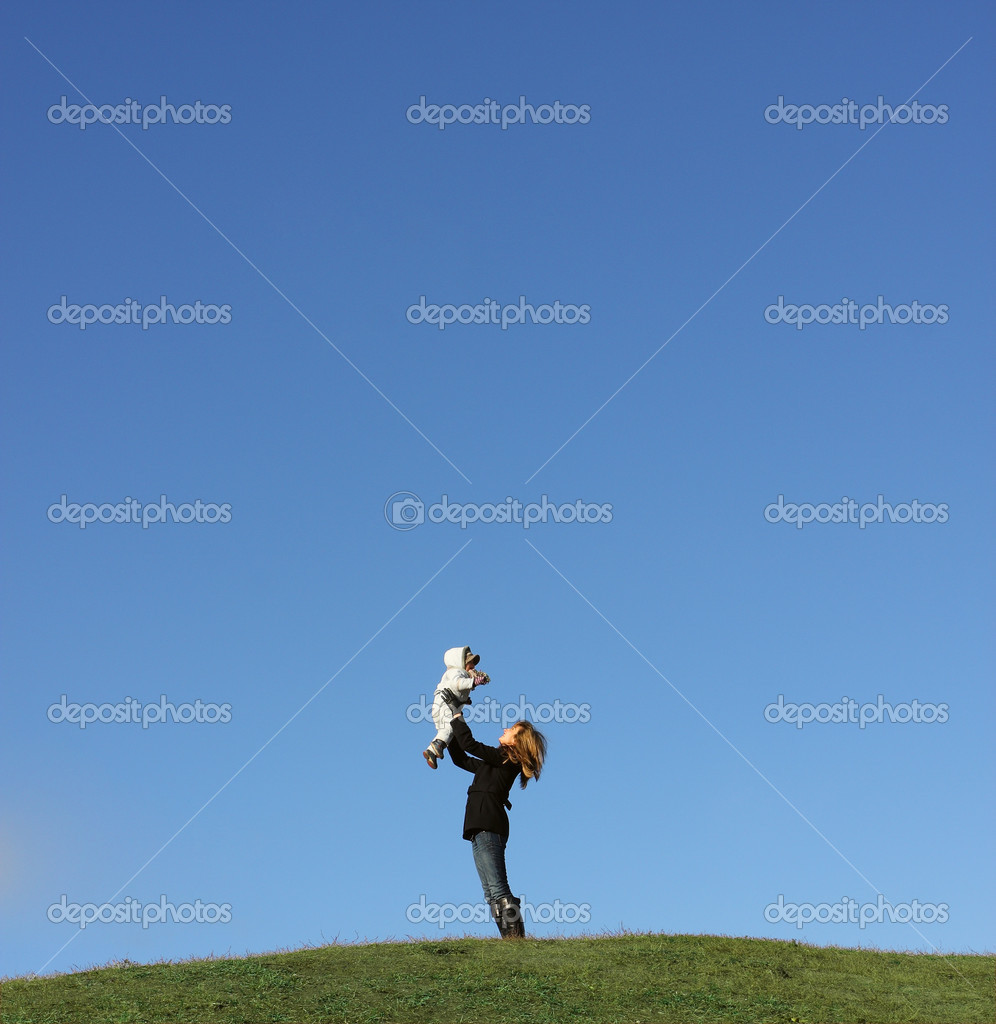 Mother lifting up her son on green hill against clear blue sky — Stock Photo #2059250