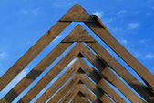 Wooden roof beams under blue skies — Stock Photo