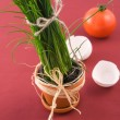 Green onion in pot with tomato - Stock Photo