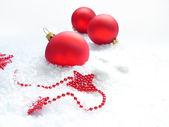 Three red balls and stars in the snow — Stok fotoğraf