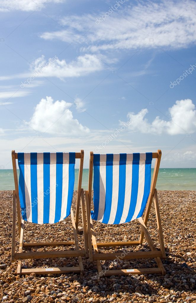A view of two empty deck chairs from behind, looking out to the sea, on a pebble beach  Stock Photo #1948635